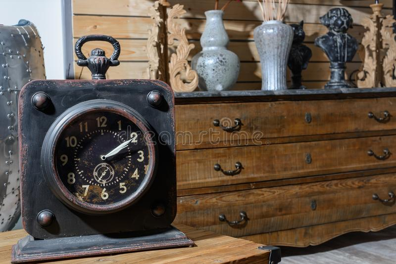 Old vintage clock on wooden table in modern retro styled. Living room stock photography