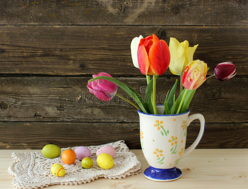 Old vintage cup, tukips and easter eggs on wooden stock images