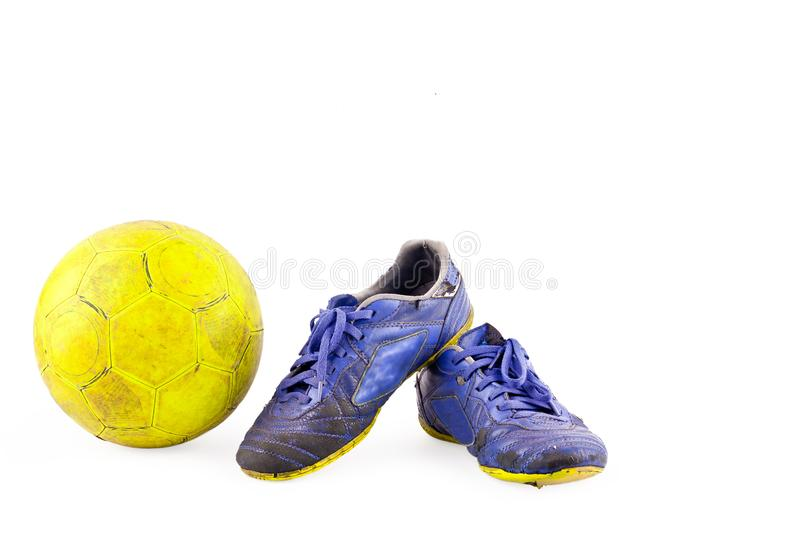 Old vintage damaged futsal sports shoes and ragged yellow ball on white background football object isolated royalty free stock images