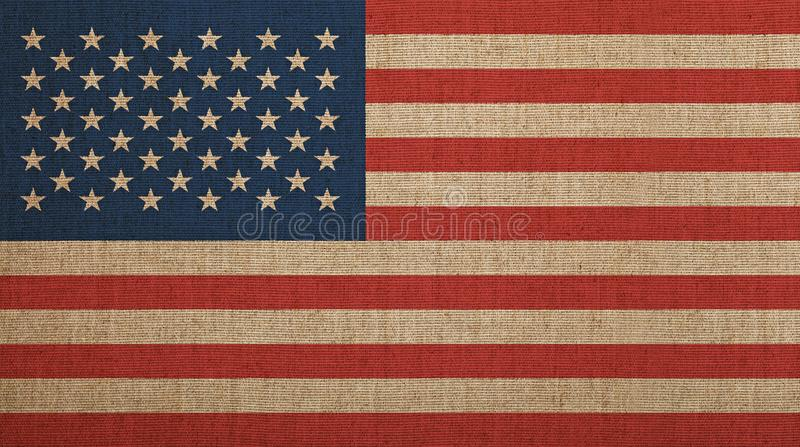 Old vintage faded American US flag over canvas. Old grunge vintage dirty faded American US national flag over background of jute linen canvas royalty free stock photo