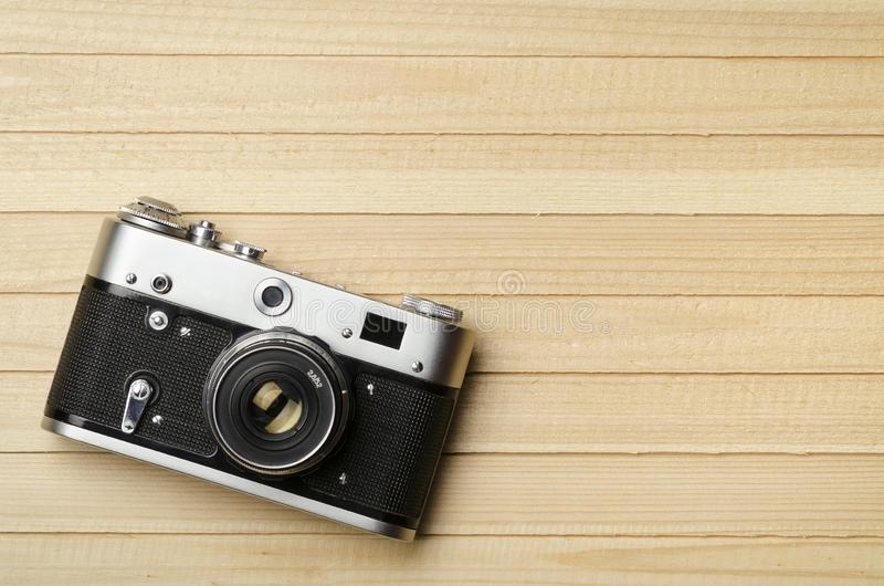 Old vintage film camera on wooden background, top view royalty free stock photos