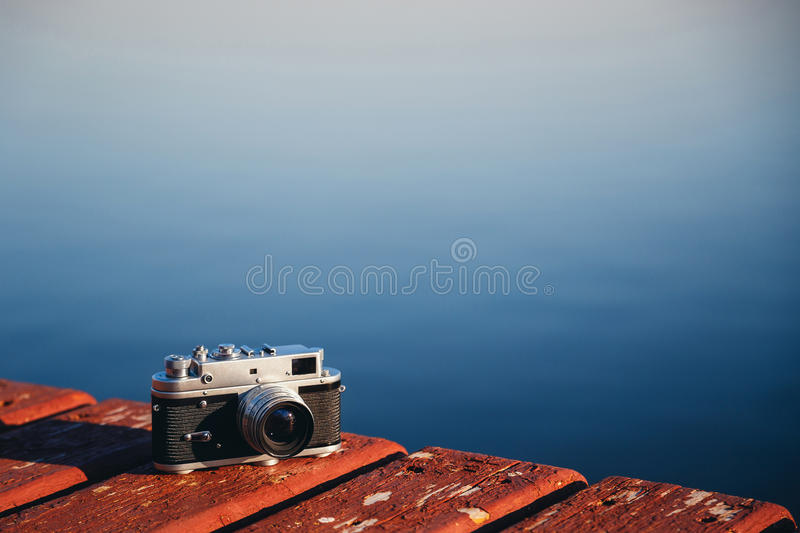Old vintage film photo camera lying on wooden berth, dark blue water background. Copy space.  royalty free stock photos