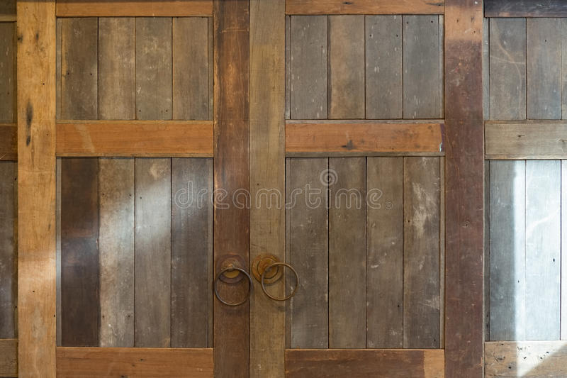 Old vintage folding wooden door. Frame with brass handle in countryside royalty free stock images