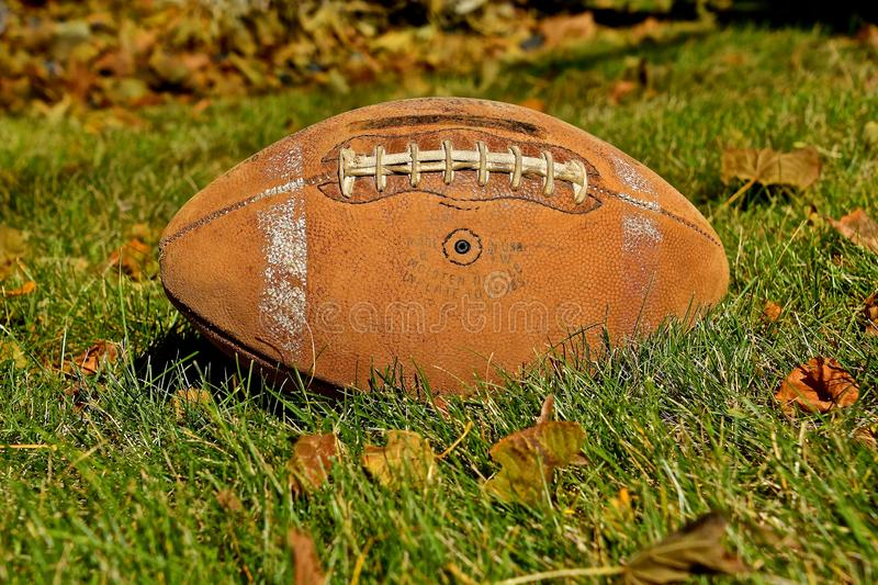 Old vintage football laying in the autumn leaves. An old football shoes bring back the autumn memories of a past era of the gridiron royalty free stock photos
