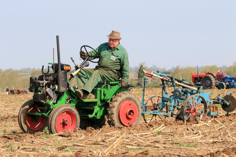 Old green trusty tractor at ploughing match. Old vintage green trusty tractor at ploughing match show. old farmer adjusting plough. vintage garden tools and royalty free stock image