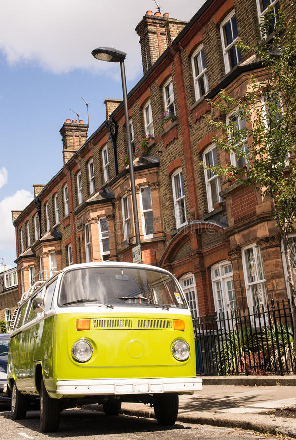 Old vintage green van parked in a street with victorian houses. In the background royalty free stock image