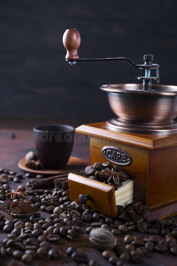 Old vintage grinder with roasted coffee beans and grind coffee on stone background. stock photo