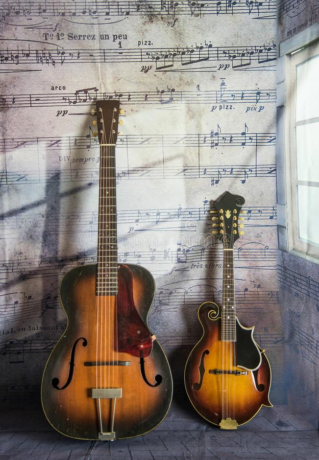 Old Vintage Guitar and Mandolin with Musical Notes. Beautiful and vintage Guitar and Mandolin with widow lighting against a music note b background royalty free stock image