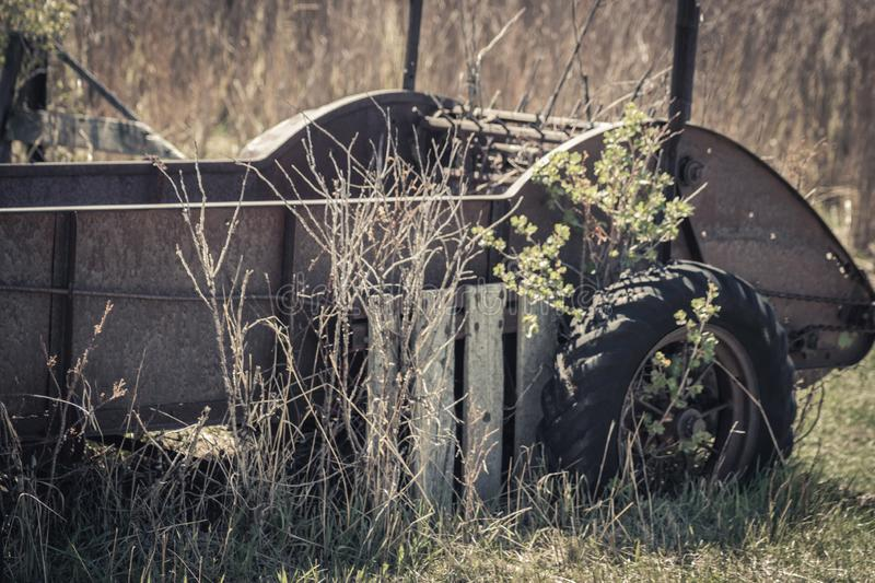Rusty Vintage Hay Baler Cart Lawn Decor. An old vintage hay baler cart sits in a field surrounded by grass and bushes. It is now being used as lawn decor and a stock image