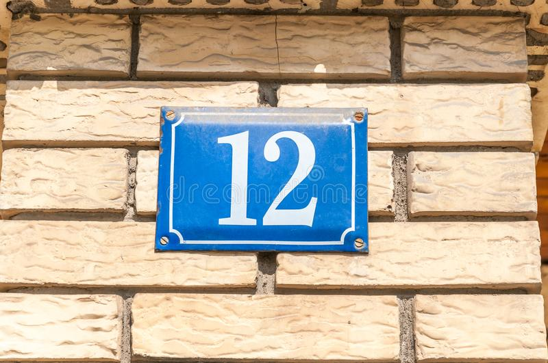 Old vintage house address blue metal number 12 twelve on the brick facade of residential building exterior wall on the street side.  stock photo