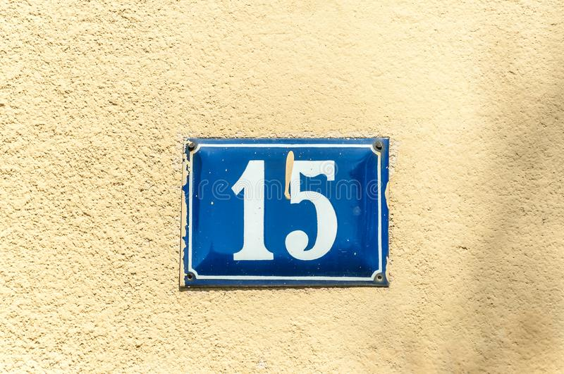 Old vintage house address metal plate number 15 fifteen on the plaster facade of abandoned home exterior wall on the street side stock photo