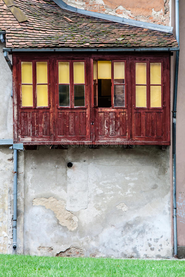 Old vintage house with wooden balcony windows and roof stock image