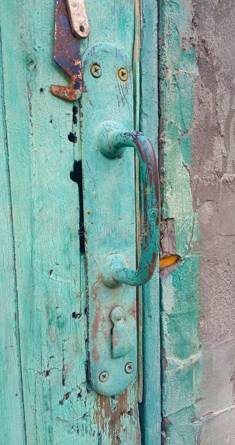 Old vintage iron shabby painted wooden door handle. The paint peeled off. The keyhole was closed by a lock in the form of a lock royalty free stock photography