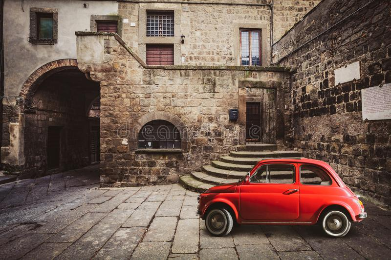 Old vintage italian scene. Small antique red car. Fiat 500 stock images