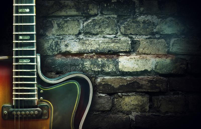 Old vintage jazz guitar on a brick wall background. Copy space. Background for concerts, festivals, music schools. Art royalty free stock image