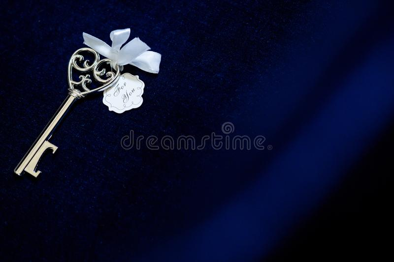 Old vintage key in satin cloth background stock images