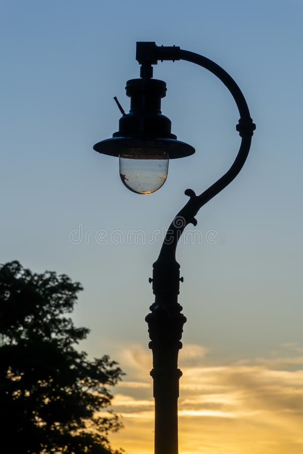 Old vintage lantern lamp post on the sunset sky background stock photo