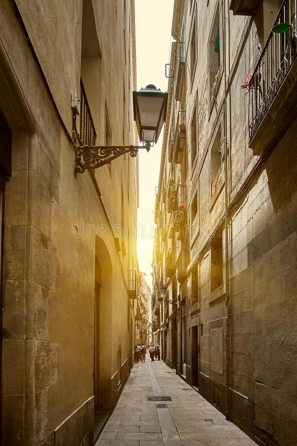 Old vintage lantern on the narrow historic street of Barcelona, Spain with beautiful sunset and bunch of tourists people on the stock image