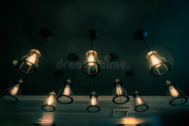 Old vintage light bulb glowing in cafe. Vintage tone stock photos