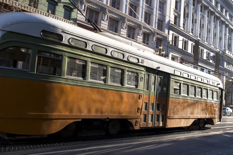 Old Vintage Looking Passenger Commuter Street Car Travels along Busy Market Street in Downtown San Francisco stock image