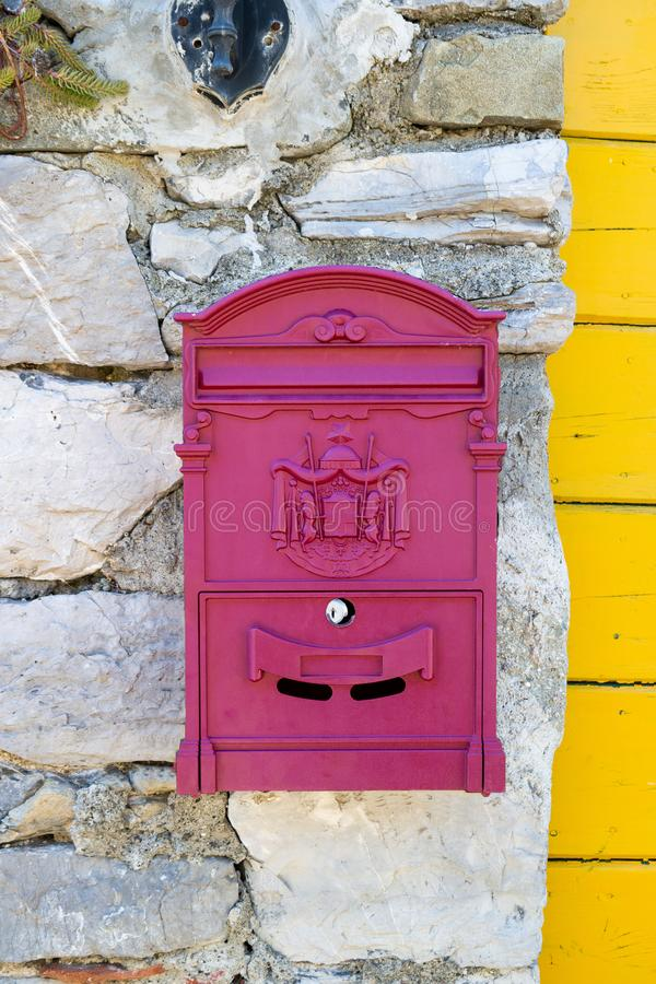 Old vintage magenta metal mail box with crest in Italy Europe ona sunny summer day front view. 2019 stock image
