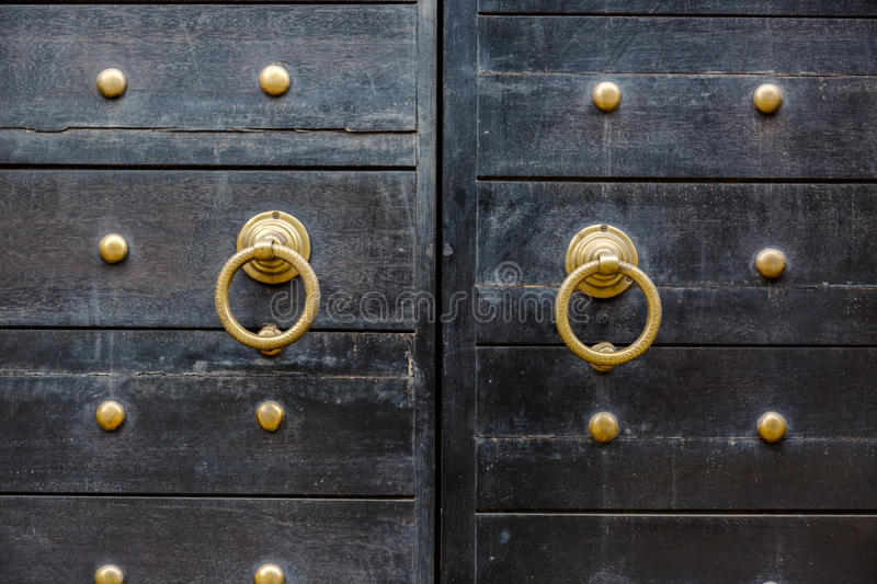 Old vintage massive wooden black door with metal locker and hand royalty free stock photography