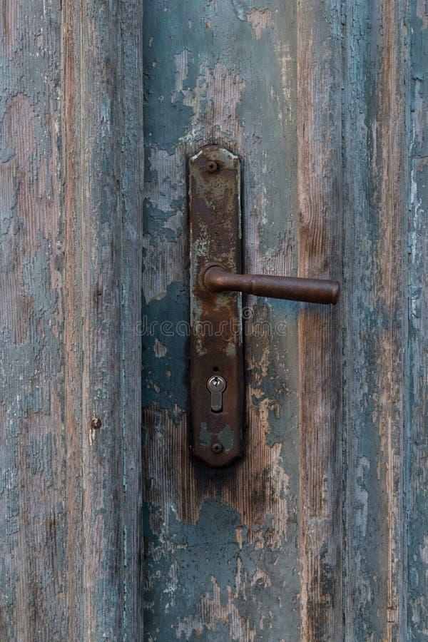Old vintage metal door handle on old blue wooden doors. Rusty door handle royalty free stock image