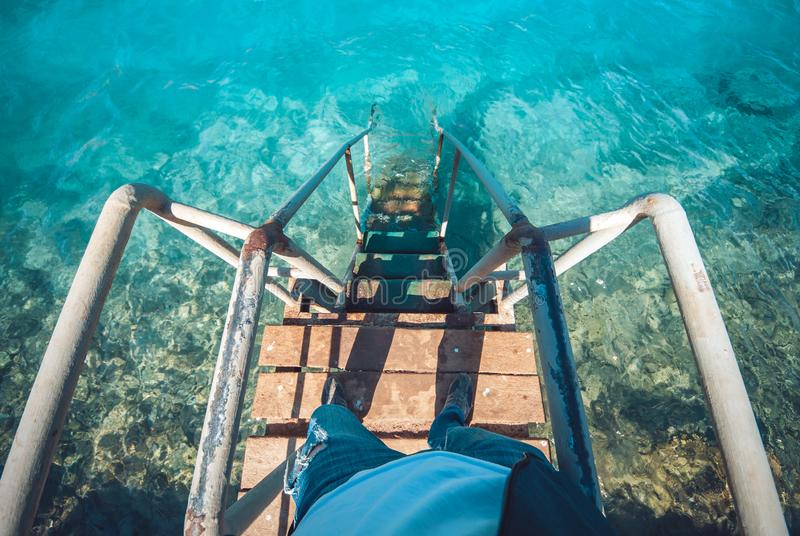 Old vintage metal wooden stairs leading to blue turquoise sea water from beach. Beautiful summer day. Swimming pool with. Grunge retro stairs on the ocean coast royalty free stock photo