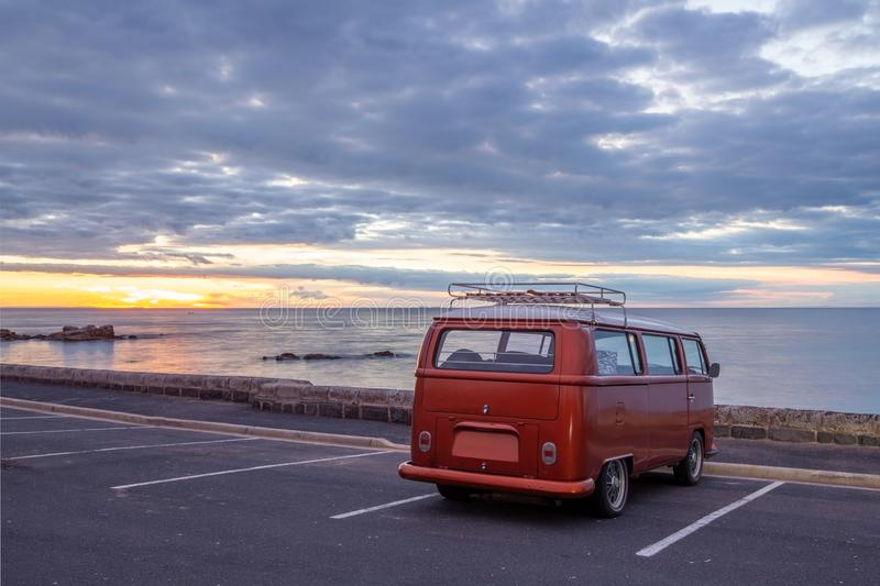 Old vintage minivan. Old vintage minivan parked at empty parking lot on the waterfront at sunset royalty free stock image
