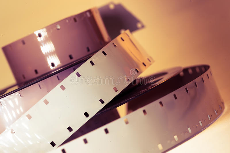 Old vintage movie camera film reel strip. In sepia cross process colors royalty free stock photography