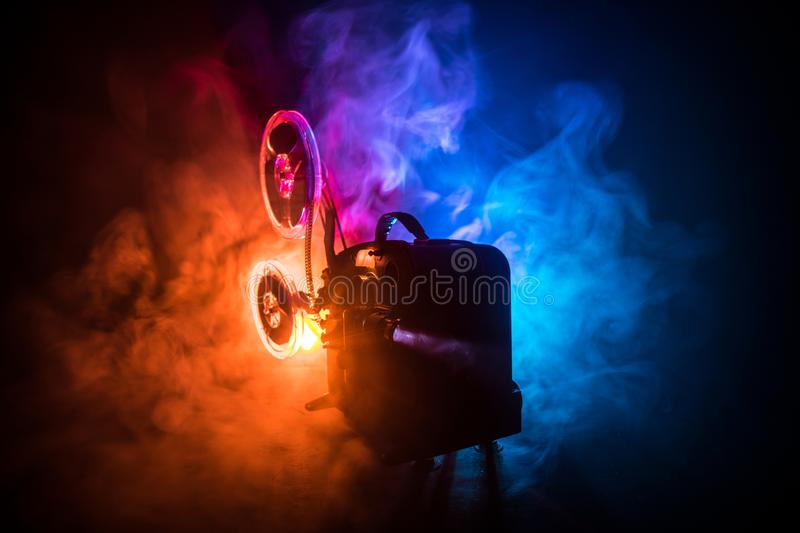 Old vintage movie projector on a dark background with fog and light. Concept of film-making. Selective focus stock image