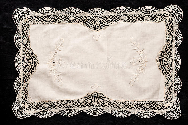 Old vintage napkin with lace border on the black wooden table royalty free stock images