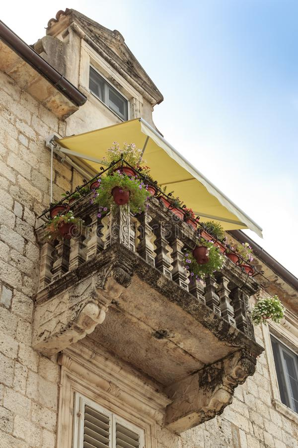 Old, vintage, ornate balcony with a modern yellow canopy in Kotor, Montenegro stock image