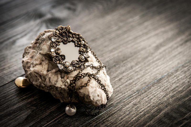 Old vintage oval mirror necklace on a stone fashion objects on wooden table. Filtered image, toned royalty free stock image