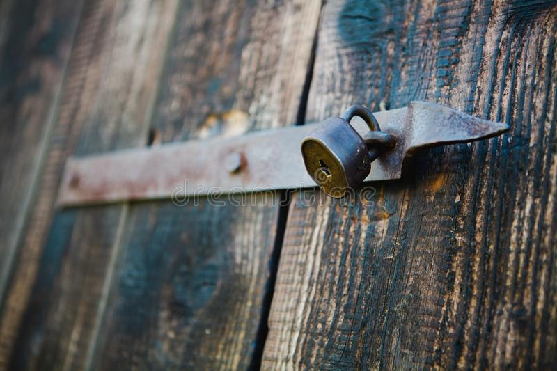 Old vintage padlock on wooden doors. Shallow focus - Rusty royalty free stock photography