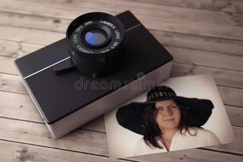 Old Vintage Photo Camera with Wooman Portrait. 3d Rendering. Old Vintage Photo Camera with Wooman Portrait on a wooden table. 3d Rendering vector illustration