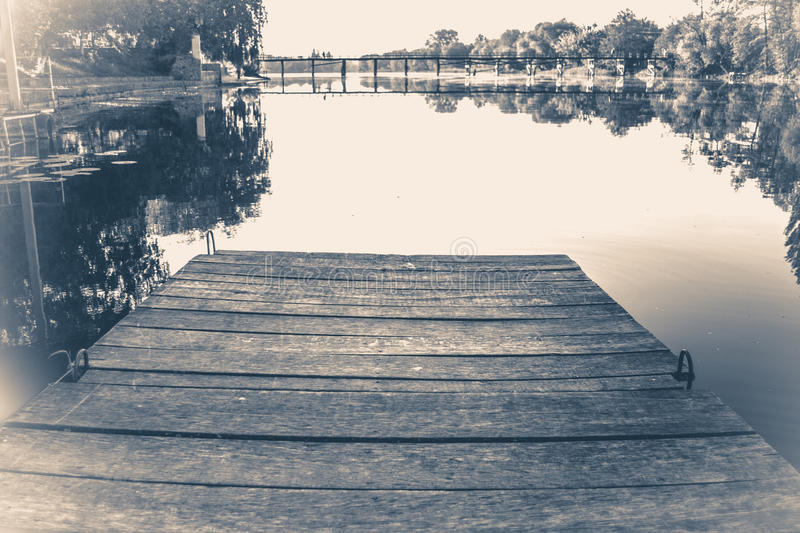 Old vintage photo. Empty wooden old berth on river. On a calm, windless day royalty free stock photo