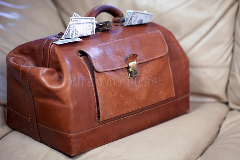 Old vintage red leather case full of money coming out of the sides. stock images