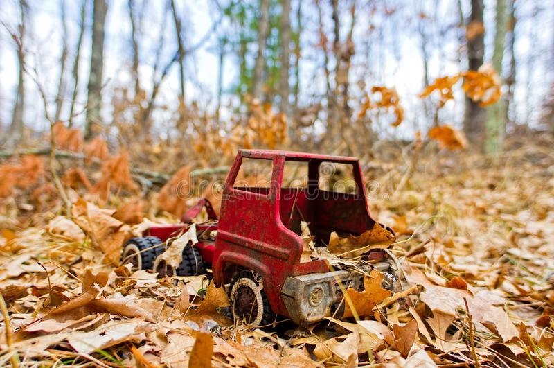 Old vintage red toy truck found in the woods near Governor Knowles State Forest in Northern Wisconsin - taken in Autumn with truck. Surrounded by Fall leaves in stock photography