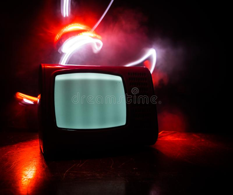 Old vintage red TV with white noise on dark toned foggy background. Retro old Television reciever no signal. Selective focus royalty free stock images