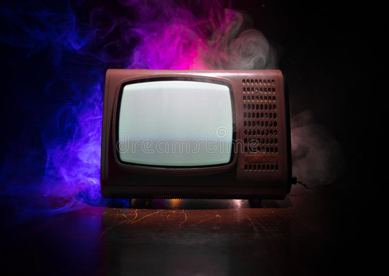 Old vintage red TV with white noise on dark toned foggy background. Retro old Television reciever no signal. Selective focus stock photo