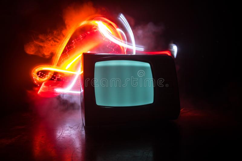 Old vintage red TV with white noise on dark toned foggy background. Retro old Television reciever no signal. Selective focus stock images