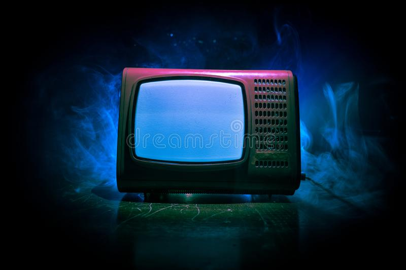 Old vintage red TV with white noise on dark toned foggy background. Retro old Television reciever no signal. Selective focus stock photography