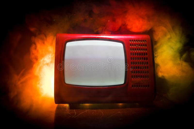 Old vintage red TV with white noise on dark toned foggy background. Retro old Television reciever no signal royalty free stock images