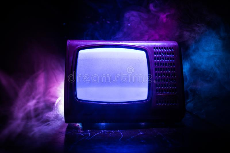 Old vintage red TV with white noise on dark toned foggy background. Retro old Television reciever no signal royalty free stock photo