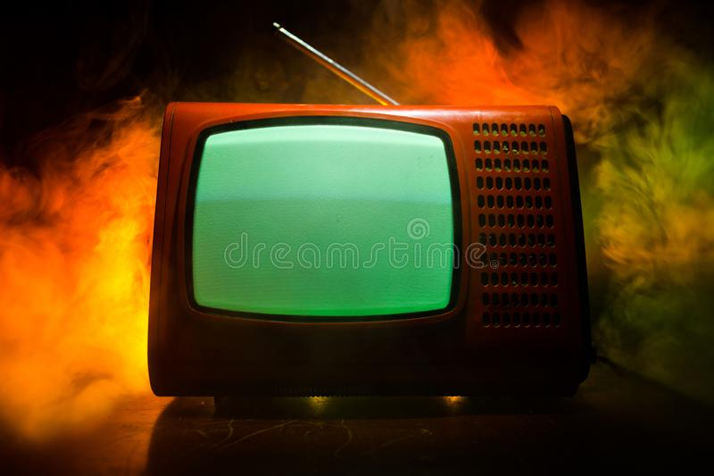 Old vintage red TV with white noise on dark toned foggy background. Retro old Television reciever no signal stock photos