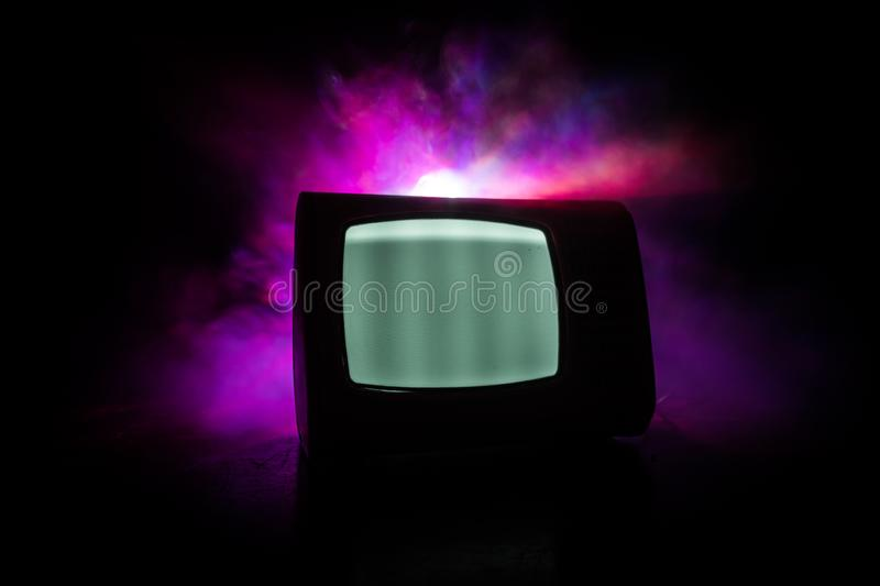 Old vintage red TV with white noise on dark toned foggy background. Retro old Television reciever no signal royalty free stock photography