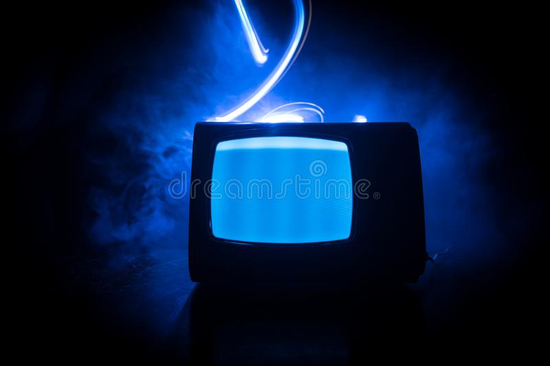 Old vintage red TV with white noise on dark toned foggy background. Retro old Television reciever no signal. Selective focus royalty free stock photos