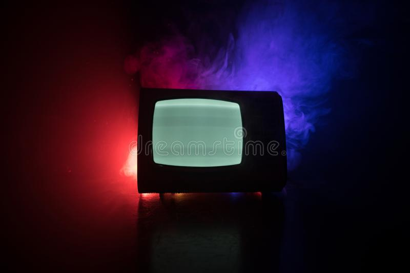 Old vintage red TV with white noise on dark toned foggy background. Retro old Television reciever no signal. Selective focus royalty free stock image