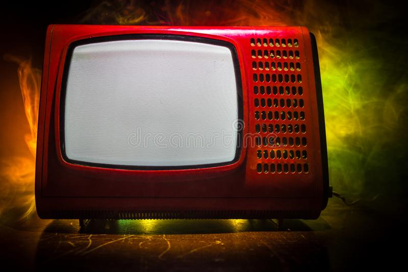 Old vintage red TV with white noise on dark toned foggy background. Retro old Television reciever no signal stock images